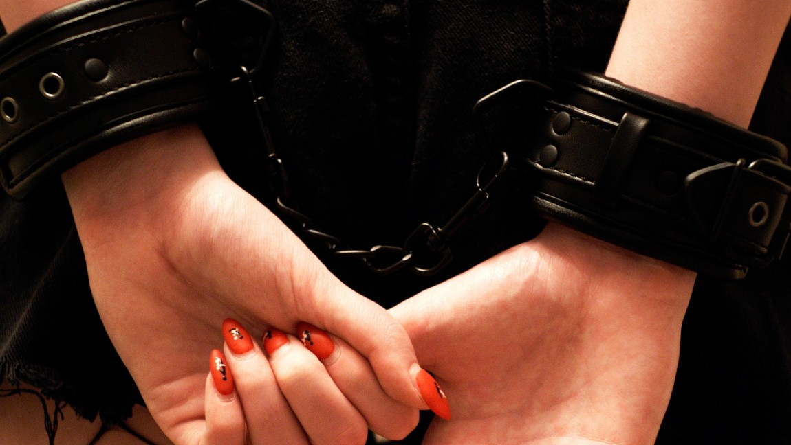 [Image description: A submissive woman's hands are cuffed behind her.] Via Unsplash