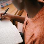 Attribution: [Image description: A picture of a woman writing in a notebook with a pen.] Via Free Photos on Pexels