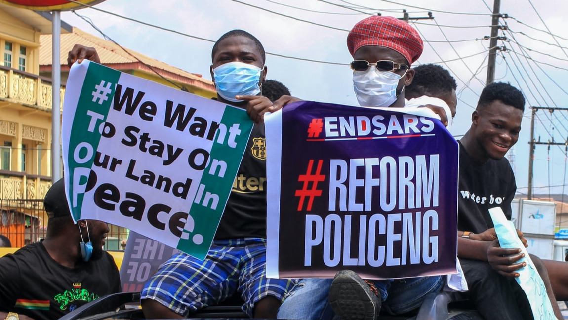 "Two people in a protest, with placards reading ""#EndSARS #ReformPoliceng"" and ""We Want To Stay On Our Land In Peace""."