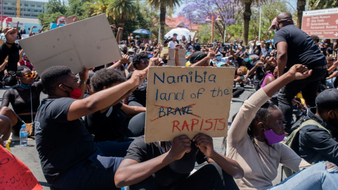 "Protester with a sign that reads ""Namibia land of the rapists"" with fists raised in the background."