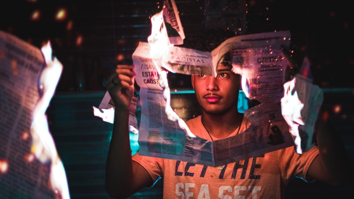 A man holding a burning newspaper.