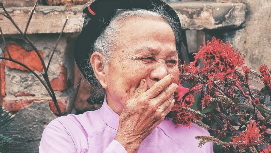 An elderly woman smiling with her hand covering her smile.
