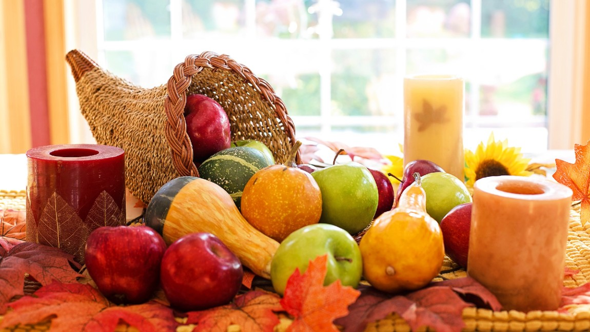 A cornucopia display of a horn-shaped basket with apples, squash, oranges, and other fruits and vegetables pouring out of it onto a table.