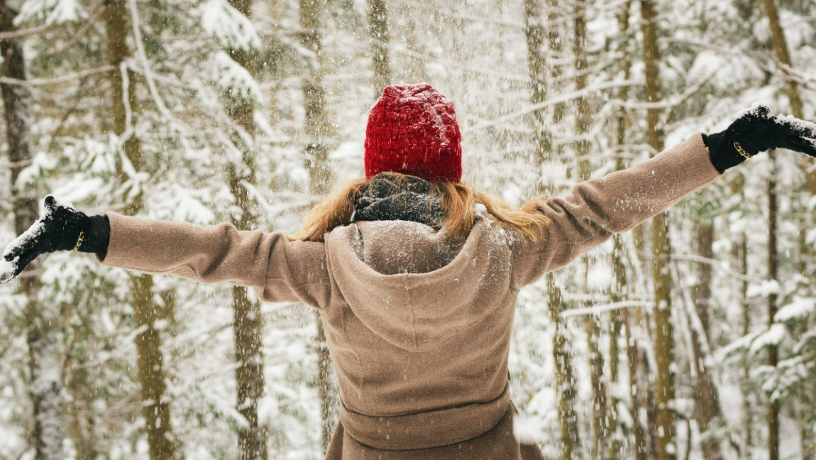 A woman stands in a snowy forest with arms outstretched.