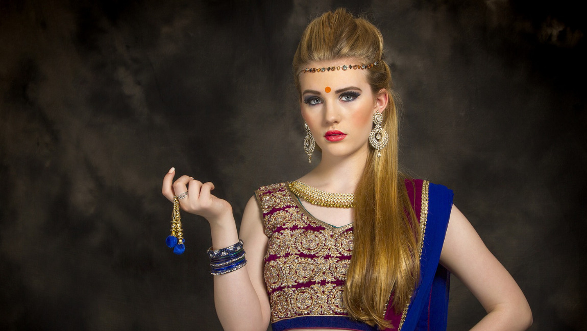 [Image Description: A white woman poses to the camera, she is wearing a traditional Indian dress, a bindi and jewelry] Via Pixabay
