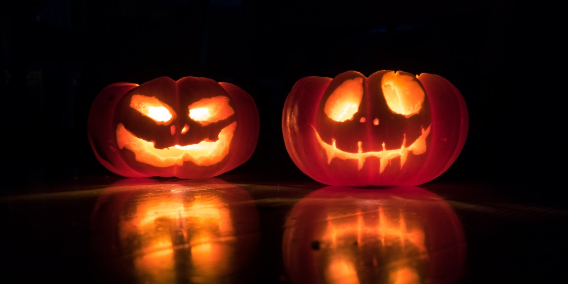 Two Jack-o-lanterns placed on a table in the dark.