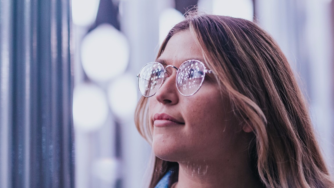 A blond woman looking up to her left thoughtfully. There are bright lights behind her and lights reflecting off her eyeglasses.