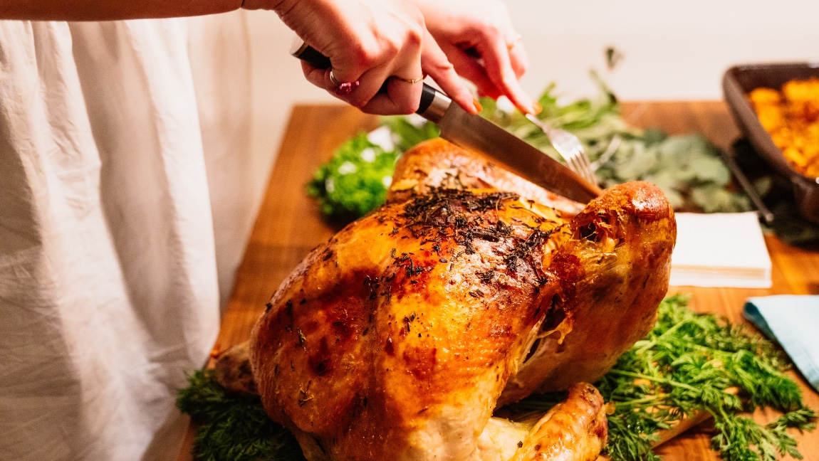 A cooked turkey on a table about to be cut with a knife by a woman.