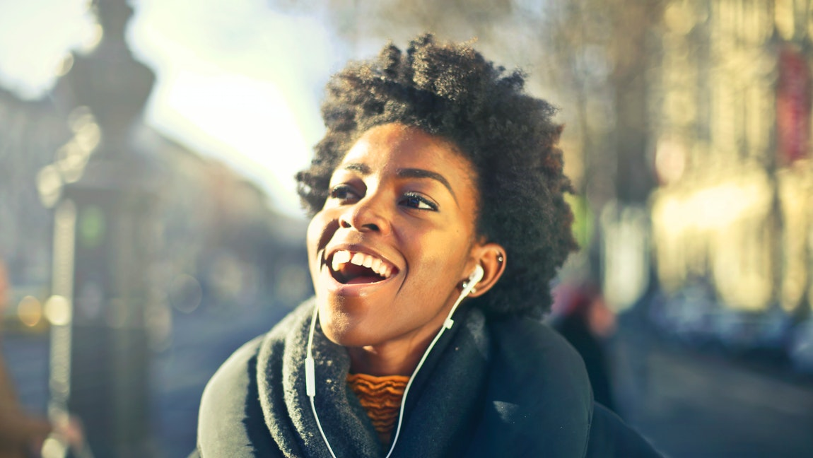 A Black woman with an afro is walking outside during the day wearing headphones and smiling brightly.