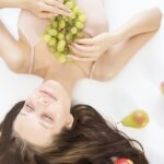 A woman laying down with a bundle of grapes in her hands with apples and pears laying beside her.