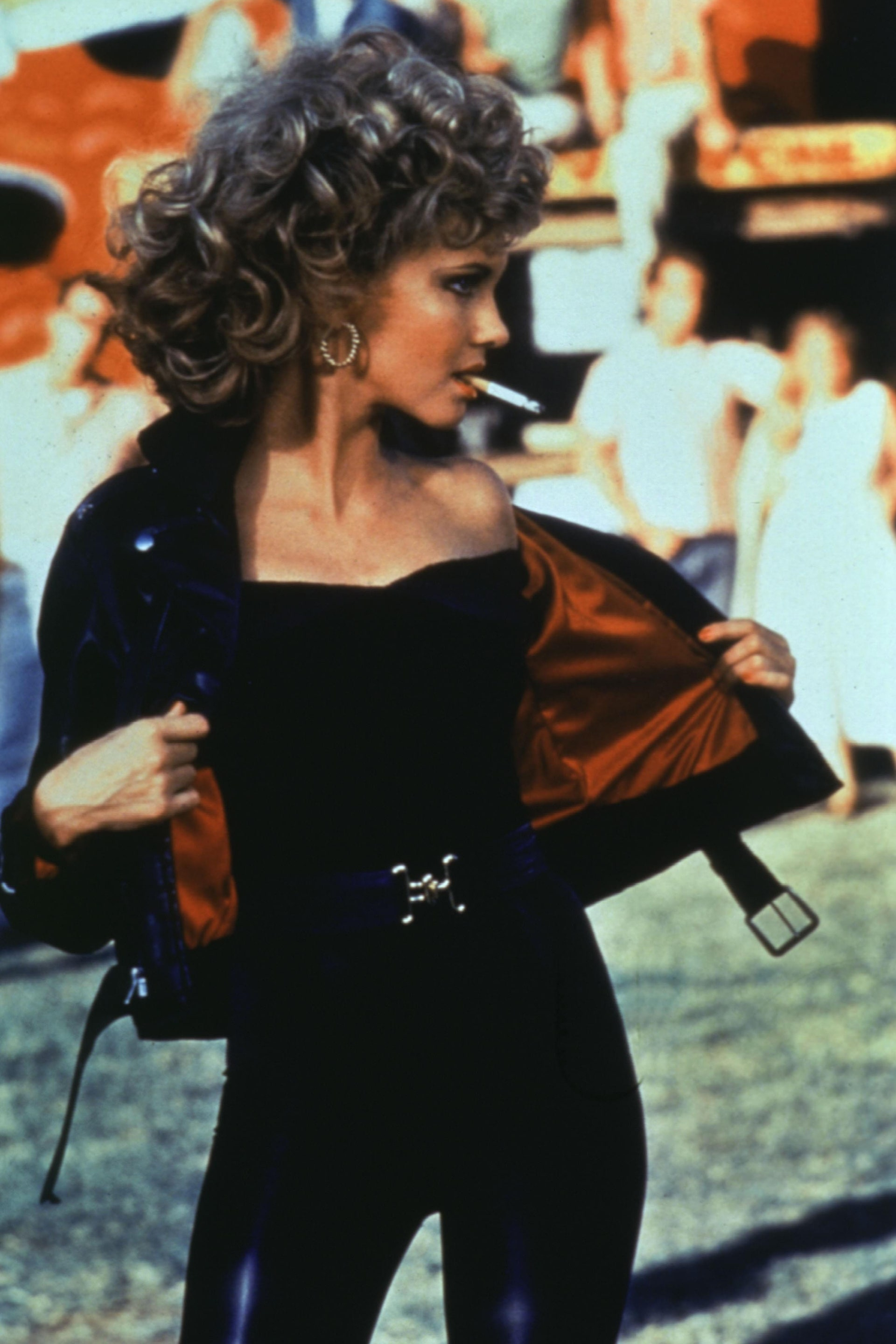 [Image Description: Sandy Olsson from Grease (1978) wearing a black body suit and jacket with a cigarette in her mouth.] via Paramount Pictures