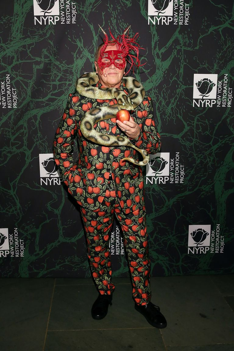Michael Kors dressed up as the The Garden of Eden, wearing a suit with apples and leaves on it, a snake around his neck, a red mask with horns, while holding an apple.