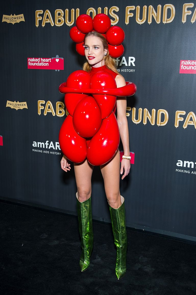 Natalia Vodianova as a Jeff Koons balloon animal, was unique and beautiful. She's wearing a red outfit made up of baubles, headgear with the same, and green leather knee-high boots to complete the look.