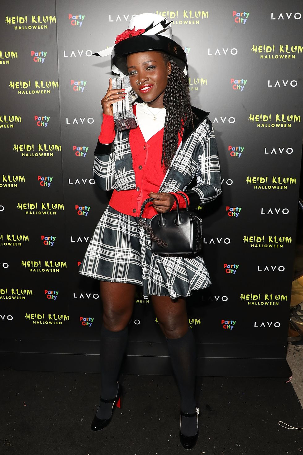 Lupita Nyong'o dressed up as Dion fromClueless. she's wearing the iconic black and white tartan mini skirt and jacket set, with a red cardigan over a white t-shirt. Her hair is braided and she's wear Dion's signature nose ring and black and white hat, as she pretends to talk on a mobile handset from the 90s.