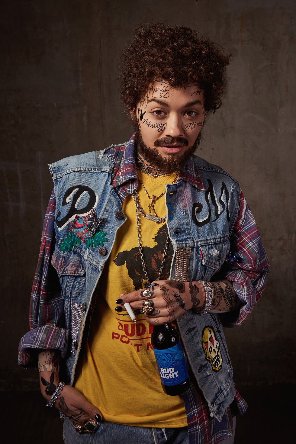 Rita Ora transformed into Post Malone with his signature tattoos, curly hair and full beard. she's wearing a denim embellished jacket over a yellow shirt, cigarette and beer in hand. It is almost impossible to tell that it's Rita under the get-up.