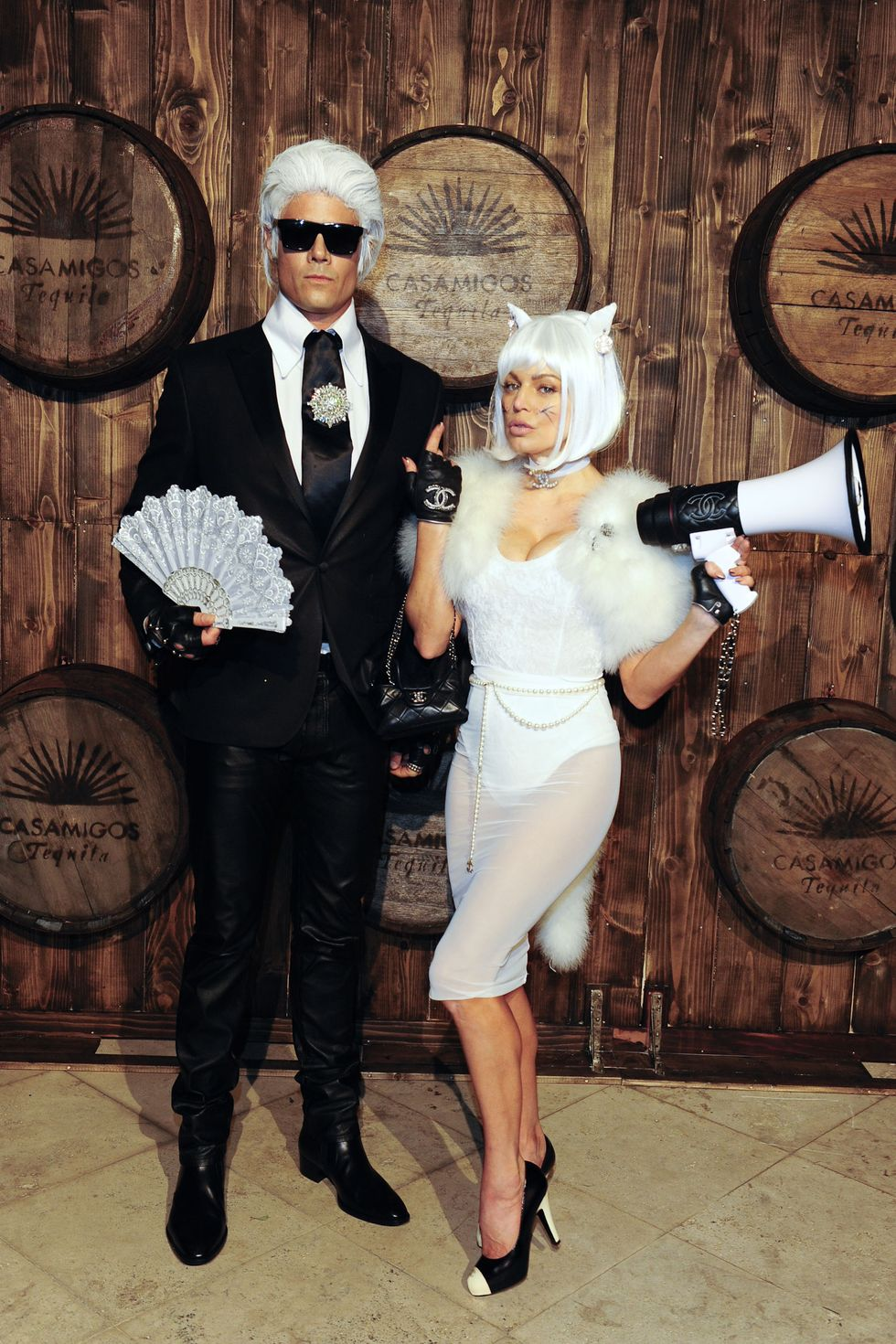 Josh Duhammel and Fergie as Karl Lagerfeld and Choupette was beautiful! He's wearing Karl's iconic white wig, black suit, with a fan in one hand. Fergie is in all white, with cat ears, a metallic white wig and a megaphone in one hand.