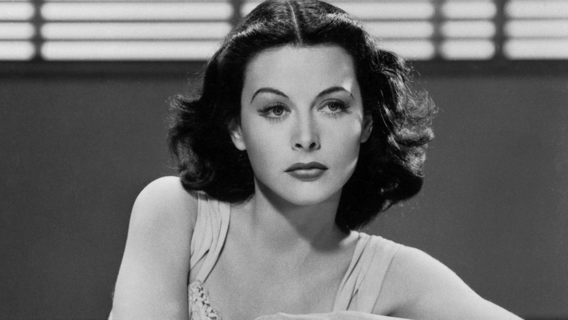 A black and white picture of Hedy Lamarr lounging on a chair wearing a sleeveless dress. She has dark, short, curly hair and is looking slightly to the right.