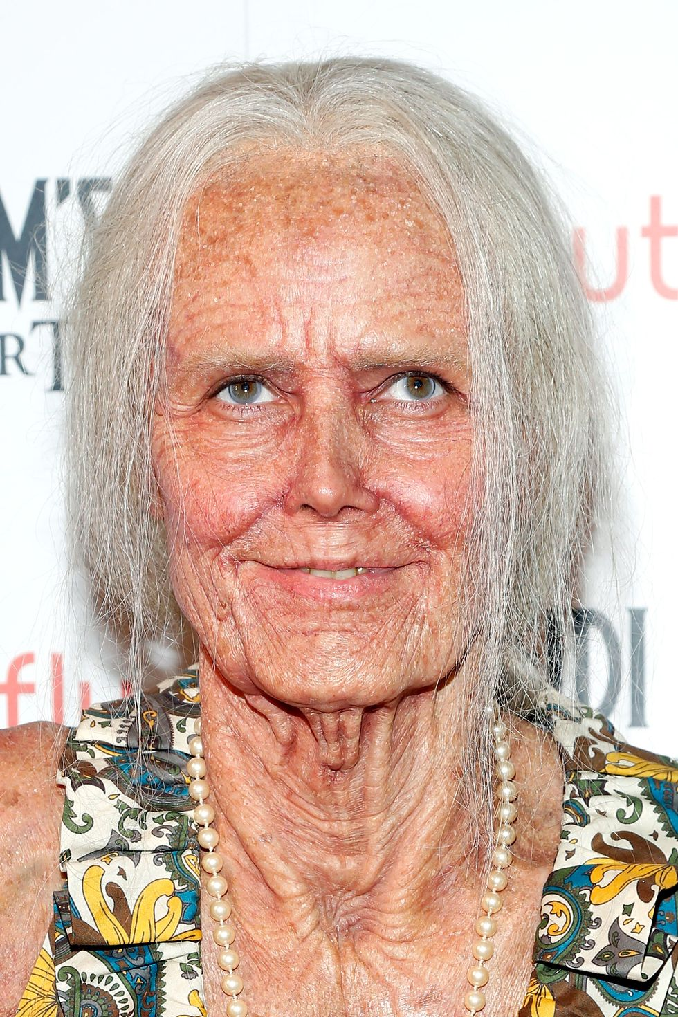 Heidi Klum as an old lady with white hair and prosthetic makeup.