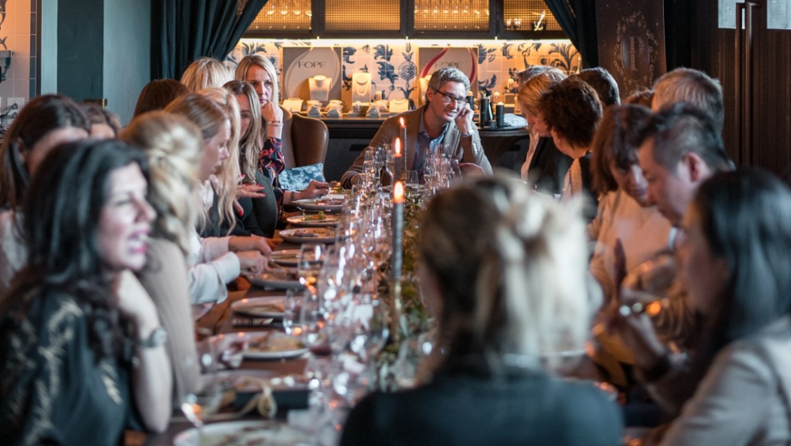 A crowd of people sit around a long dinner table that has place settings for a meal.