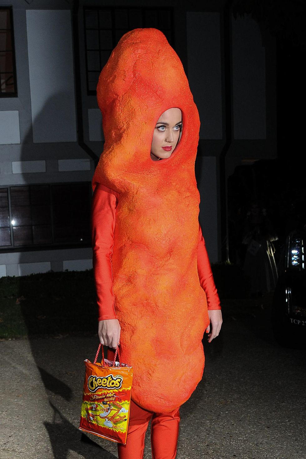Katy Petty looking funny, dressed as an orange Cheeto. She's wearing head-to-toe orange and holding a bag of Cheetos.