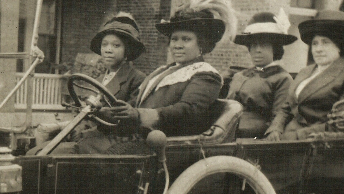 Madam J. Walker driving a car with three other black women in the car.