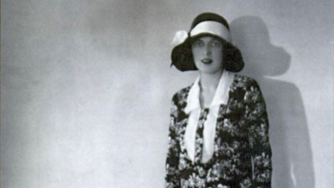 Black and white photograph of Mary Phelps Jacob, also known as Caresse Crosby, standing by a wall and wearing a dark hat and patterned dress. She is standing by a wall with her dog.