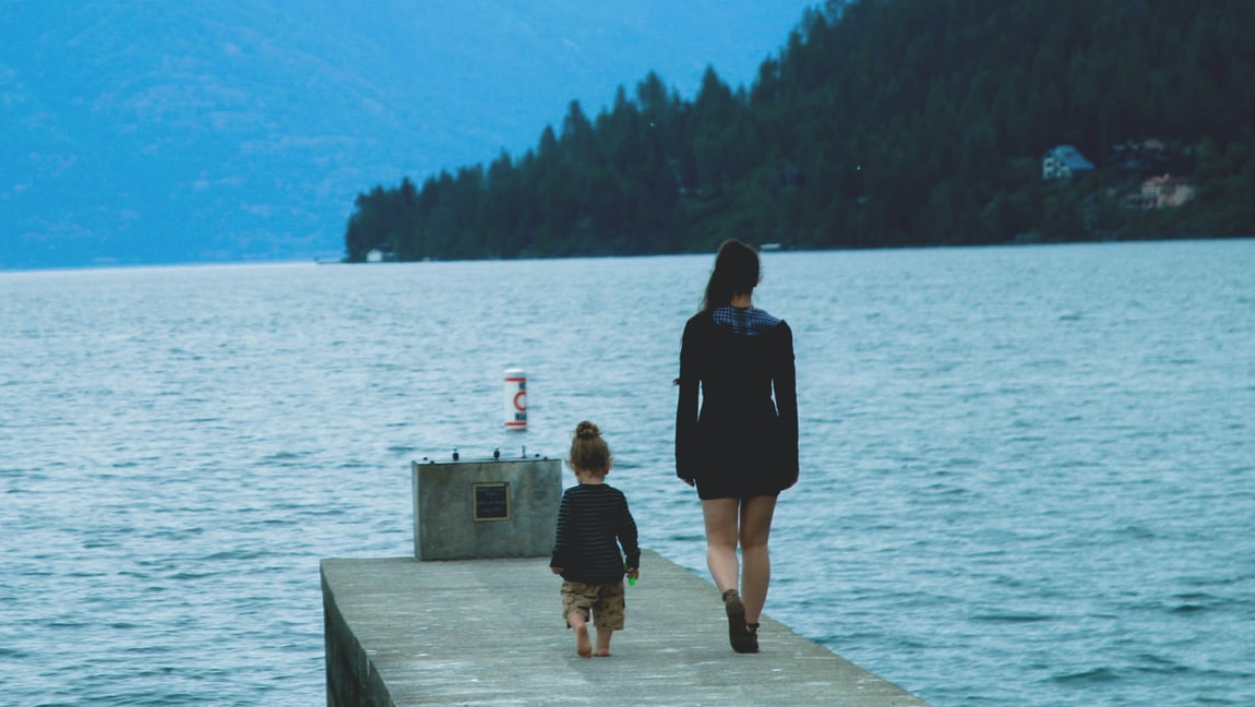 A woman with her child walking along a dock.