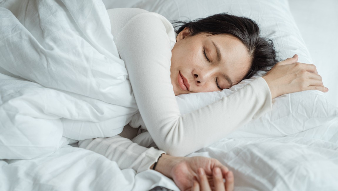 A woman wearing a white shirt is sleeping on a bed with white sheets during the daytime.