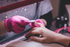 [Image description: a close up image of someone wearing pink gloves and filing another person's nails.] via Pexels
