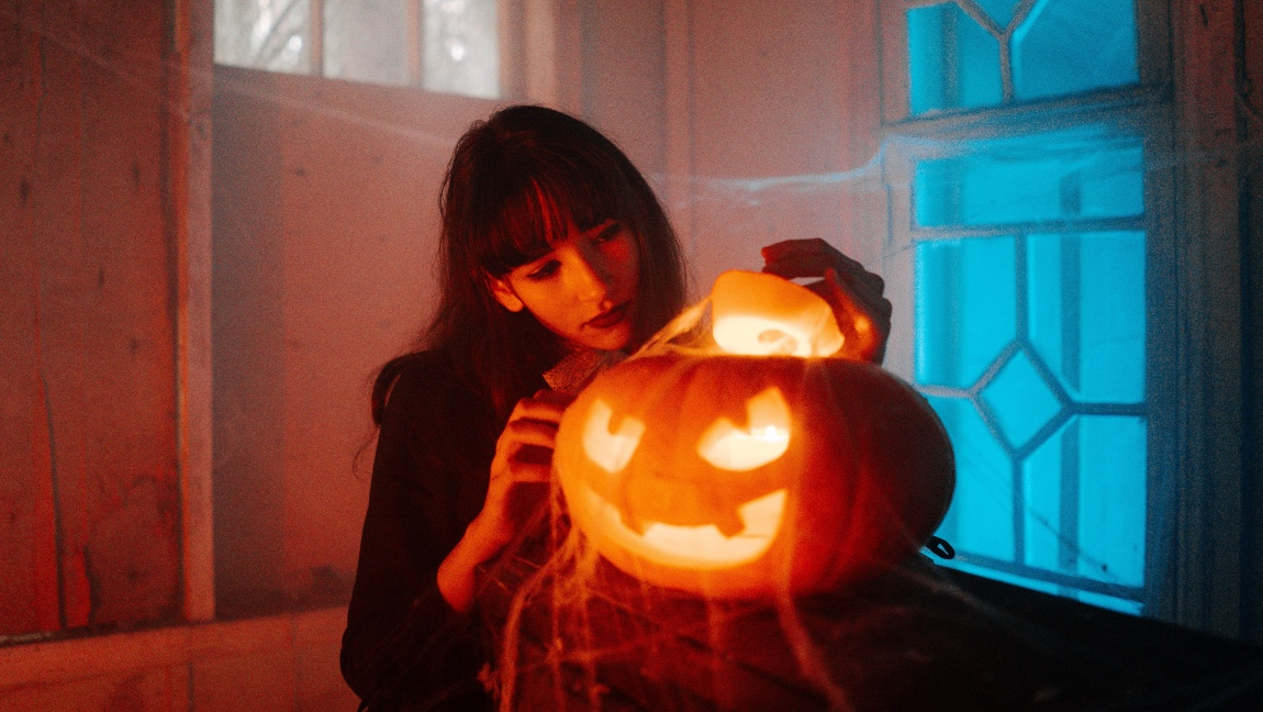 A girl in a dark room posing with a glowing jack-o-lantern.
