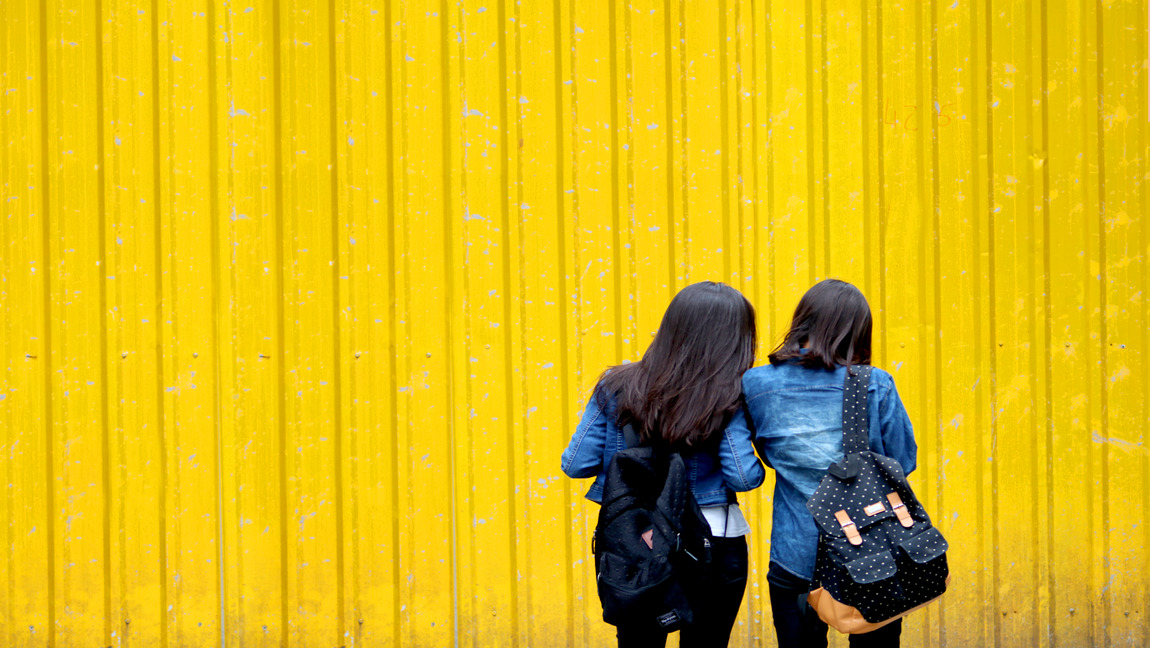 two women stand together in front of a yellow wall, their backs face the camera.