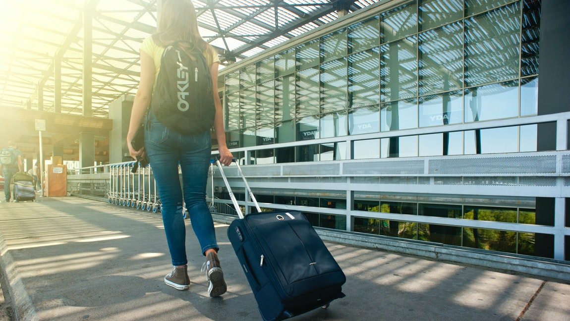 A young woman walking towards the airport with a backpack and a suitcase.