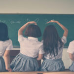Photo of four girls wearing school uniforms and doing hand signs
