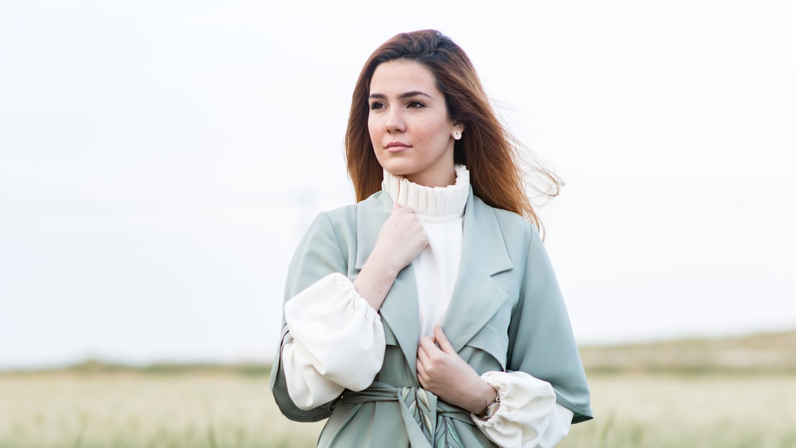A woman wearing a blue coat and white sweater stands in a field.