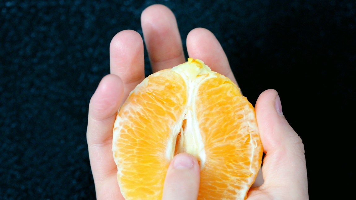 [Image description: A person is holding an orange that resembles the vulva.] Via Unsplash
