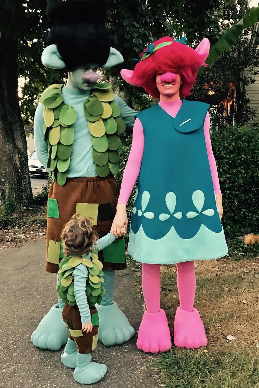 Justin Timberlake and Jessica Biel with their daughter transformed into Branch, Poppy and Lil' Branch from the Trolls. Justin is all blue in the leafy vest, matching his daughter, while Jessica is all pink wearing a teal dress and pink Troll hair.