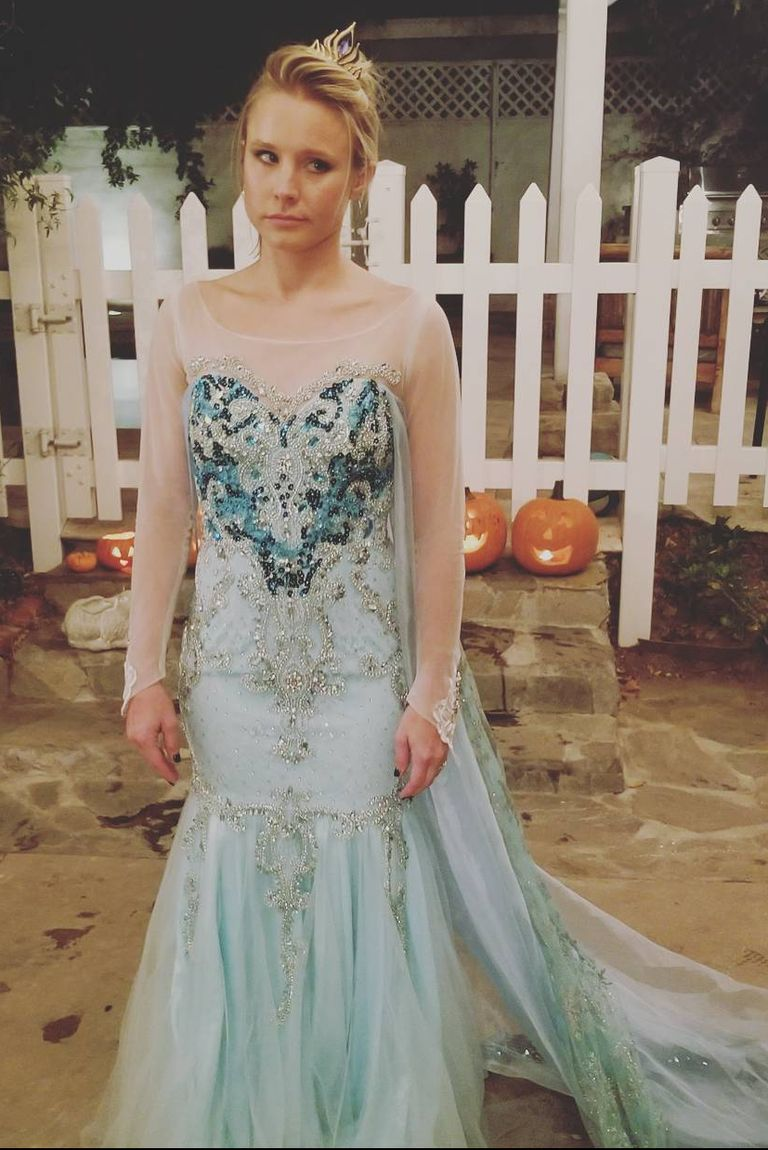 Kirsten Bell is dressed as Elsa in a blue Frozen gown, with a crown. She has a sardonic expression on her face as she is actually the voice of Anna in the movie.