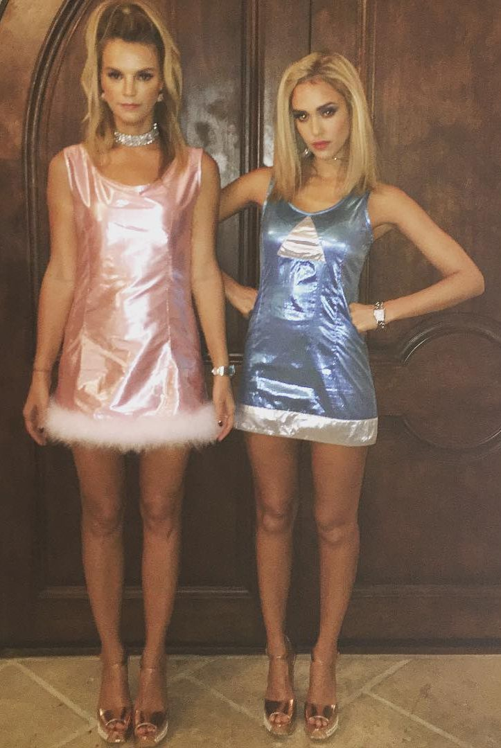 Jessica Alba and Kelly Sawyer dressed as Romy and Michele from the movie with the same title. They're in shimmery blue and pink outfits respectively, with golden platform heels and big blond hair. Very 90s outfits, just like the movie.