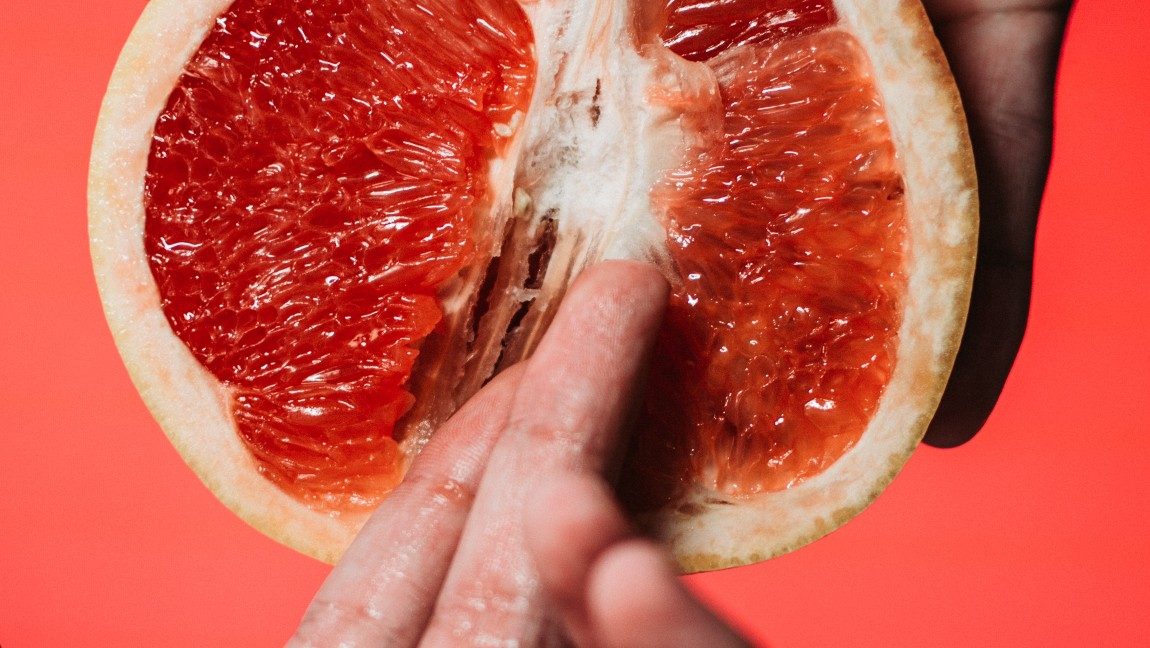 [Image description: A grapefruit with two fingers on it.] Via Unsplash