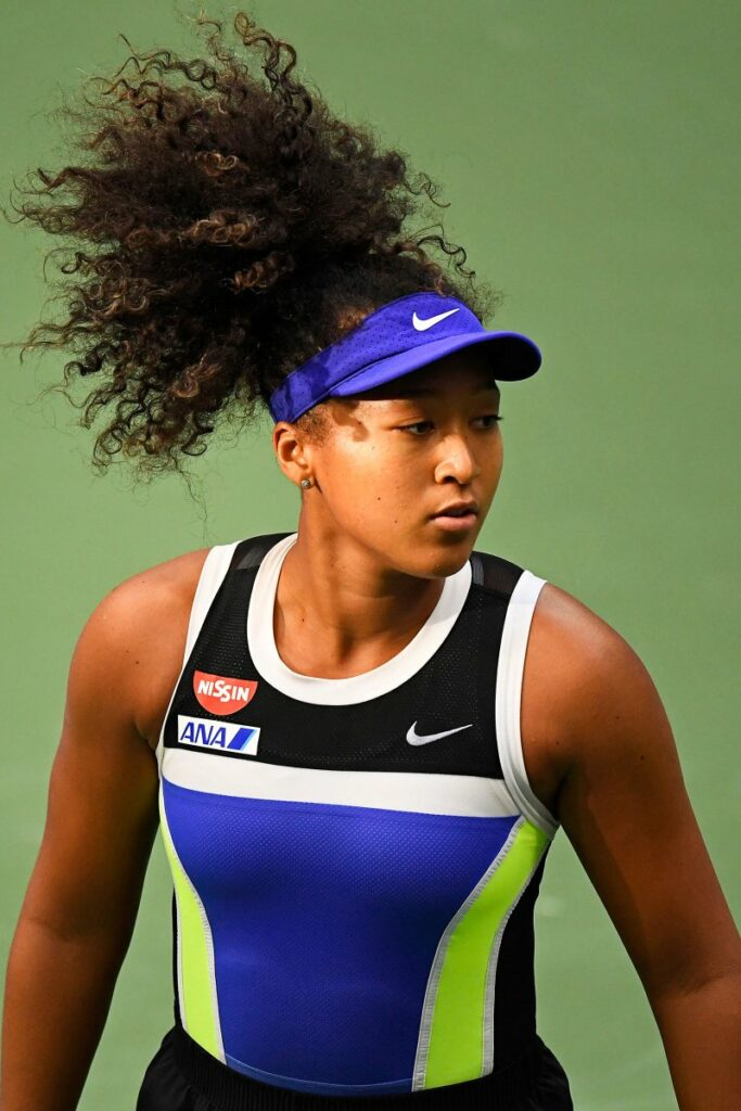 Naomi Osaka wearing a black and blue tank and blue hat during one of her matches