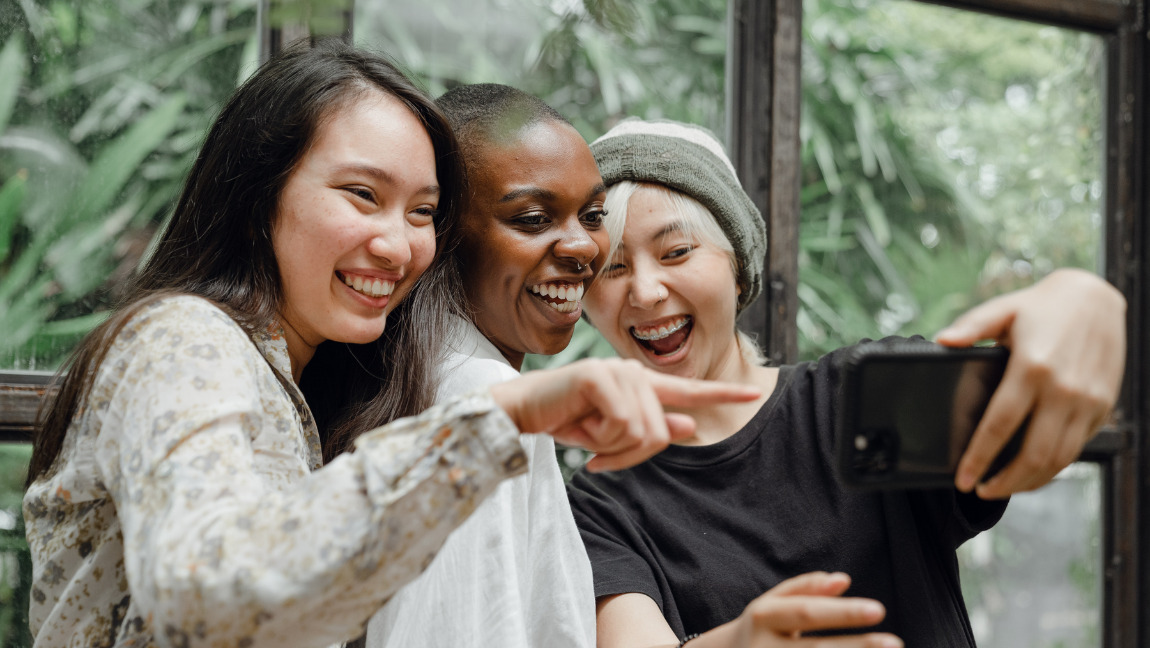 [Image description: Three women smiling while looking at a phone.] Via free images on Pexels