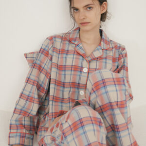 White woman with dark brown hair wearing coral flannel pajamas
