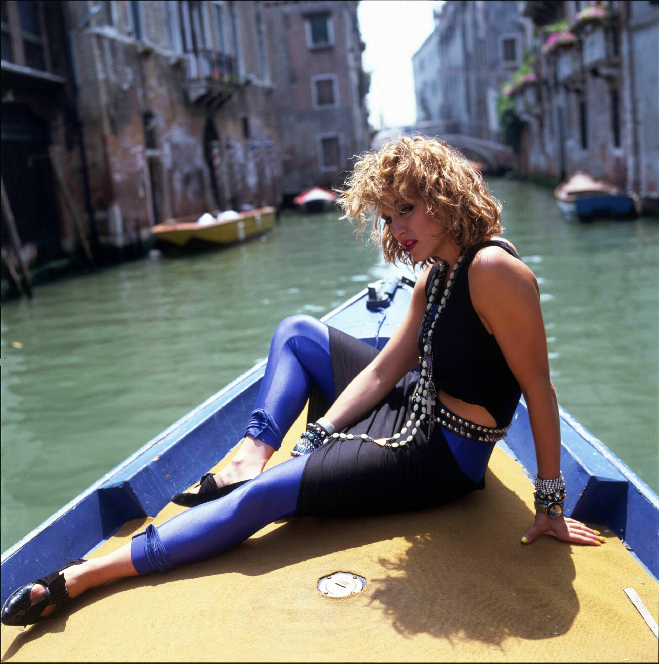Madonna wearing a black dress and bright blue leggings, 1984] via 'Like a Virgin' official music video