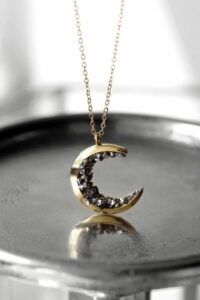 Image Description: A celestial moon necklace lined with grey stones. It is gothic themed and placed on a metal tray. [Via Etsy]