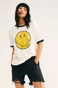 Asian woman modeling a smiley face tshirt that is white. It has a black trim around the collar and sleeves.