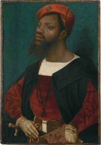 [Image description: 'Portrait of an African man' painting by Jan Mostaert (circa 1525-1530). The man is wearing loose long-sleeve garment the early renaissance era. via Wikimedia Commons