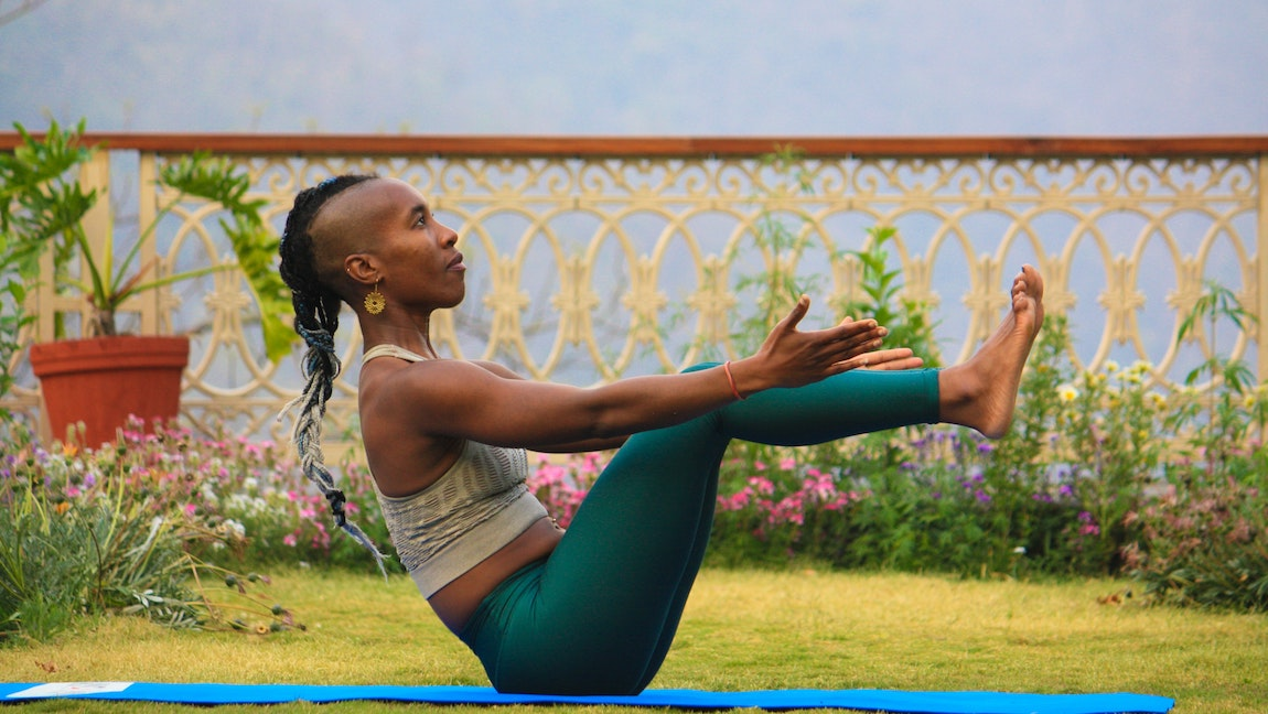 A lady wearing a light green crop top and deep green leggings does a yoga pose on a blue mat on the grass outside