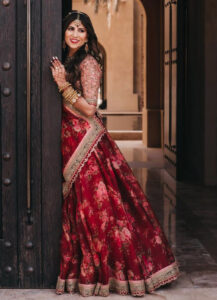 A bride wearing a red, floral lehenga