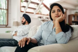 [Image description: a frustrated man and woman sitting on a couch and facing away from each other.] via Pexels
