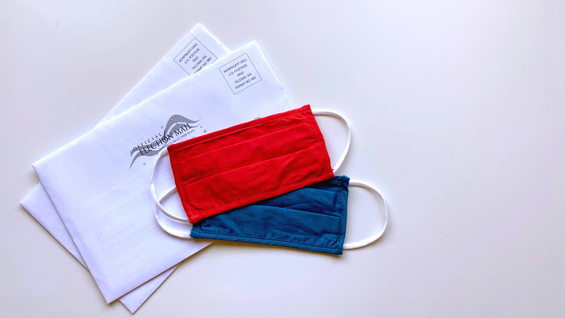Vote envelopes are placed underneath red and blue masks